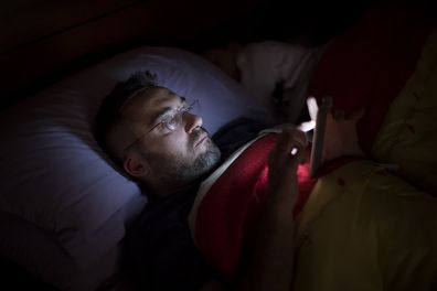 Man on phone in bed at night