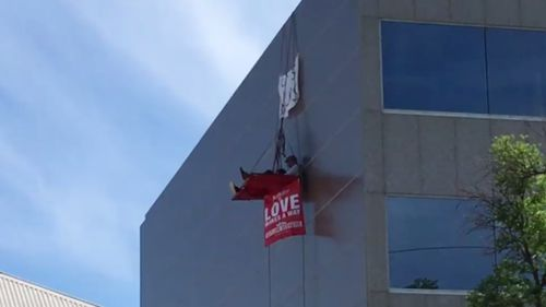 Two men are hanging in the tent above Bishop's Subiaco office in Perth. (9NEWS)