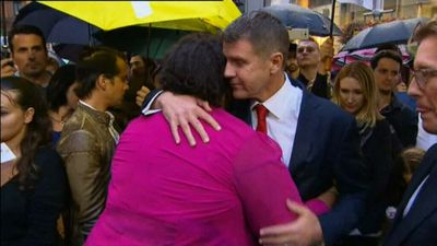 NSW Premier Mike Baird hugs a mourner at the service. (9NEWS)