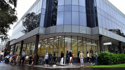 People are seen queuing outside a Centrelink office in Bondi Junction,