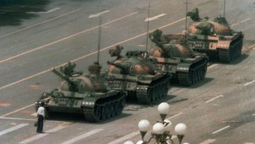 A Chinese man stands alone to block a line of tanks heading east on Beijing's Changan Blvd. in Tiananmen Square. The man, calling for an end to the recent violence and bloodshed against pro-democracy demonstrators, was pulled away by bystanders, and the tanks continued on their way.