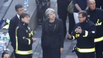 British Prime Minister Theresa May meeets firefighters as she visits the remains of Grenfell Tower, a residential tower block in west London which was gutted by fire on June 15, 2017. (AFP)