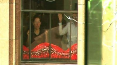 More of the hostages at another window of the cafe.