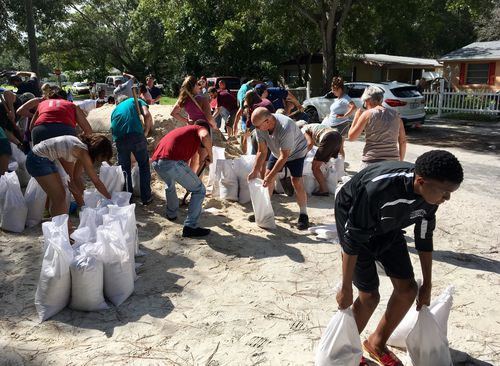 Joseph, Jr., right, 15, of St. Petersburg, bends down to carry sandbags to his family's vehicle at Lealman Community Park in Florida. (AP)