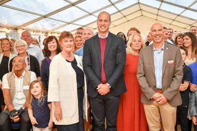 Prince William poses for a group photograph during a visit to the Fire Fighters Charity's Harcombe House.