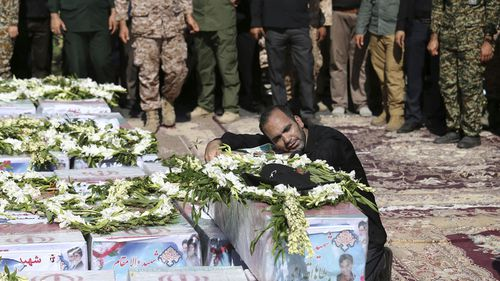 The father of Mohammad Taha Eghadami, a 4-year-old boy who was killed in the terror attack on a military parade, mourns over his coffin.