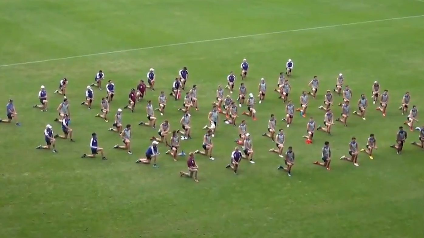 Brisbane Lions players and staff take a knee