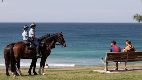Mounted police patrol a mostly empty Bondi Beach and speak to people about  NSW social distancing laws.