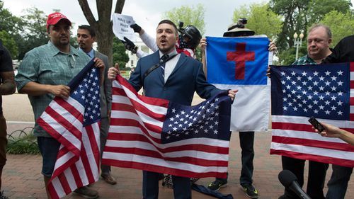 One year after the racially-stoked Charlottesville violence, a contingent of about 30 white nationalists is marching down a Washington street toward the White House surrounded by a protective bubble of police officers and vehicles.