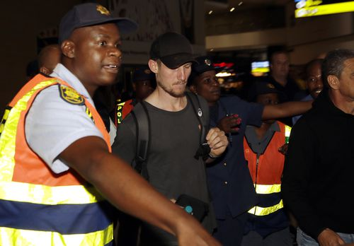 Cameron Bancroft was surrounded by security as he departed the country. (AAP)