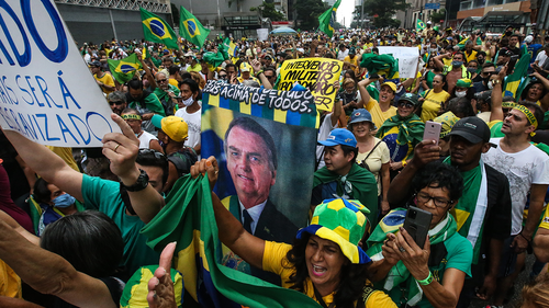 Supporters of Brazilian President Jair Bolsonaro protest and hold banners during a motorcade and demonstration in favor of the government amidst the coronavirus (COVID-19) pandemic in Avenida Paulista on March 14, 2021 in Sao Paulo, Brazil.  (Photo by Alexandre Schneider/Getty Images)