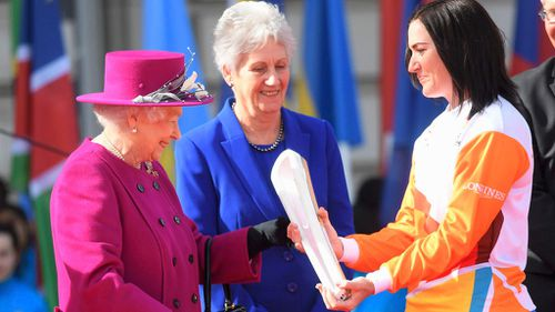 The Queen hands over the baton to cyclist Anna Meares. (AAP)