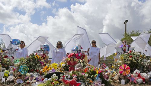 People dressed in white costumes as angels stand by a makeshift memorial outside Marjory Stoneman Douglas High School. (AAP)