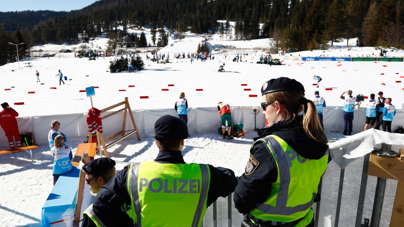 Austrian Federal Police officers stand at the finish area of a men's cross country skiing