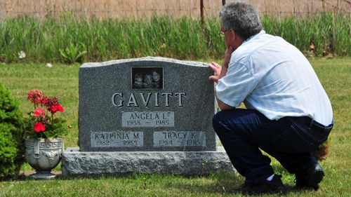 David Gavitt visits the grave of his wife and two daughters in Michigan. (AP).
