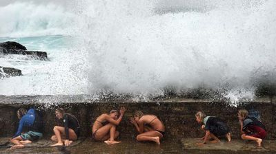 Kids take cover from waves whipped up by Cyclone Marcia on the Gold Coast. (AAP)