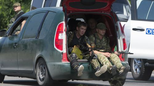 Pro-Russian rebels pass the OSCE convoy. (AAP)