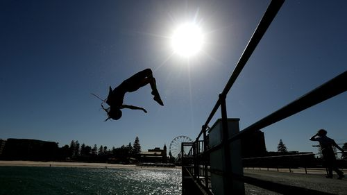 Beachgoers are seen jumping off a jetty at Glenelg Beach in Adelaide.