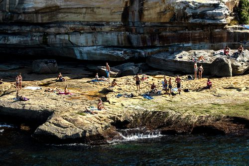 People are seen on rocks at the south end of Bondi Beach in Sydney, Australia.