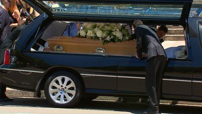 The coffin is loaded into the hearse following the service. (9NEWS)
