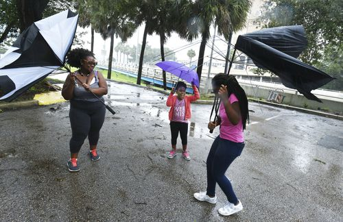 Umbrellas held by Janesse Brown, left, and her daughter Briana Johnson, 12, right, get torn apart by strong winds as Kyra Johnson, 8 watch, while they tried to visit Southbank Riverwalk in Jacksonville. (AP)