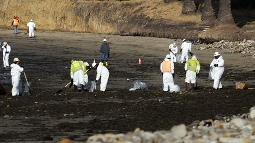 Workers have been sweeping popular tourist beaches as the oil reaches the shore. (AAP)
