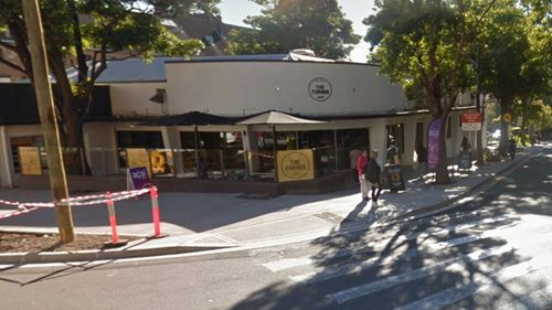 A woman has been stabbed in the neck outside a Sydney cafe.