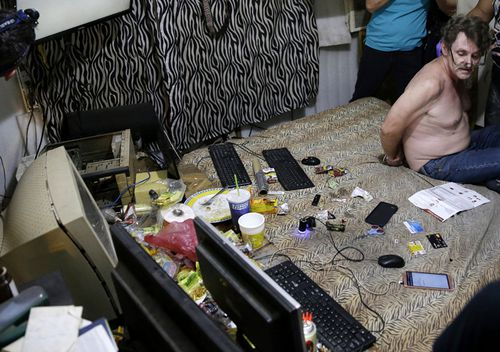 David Timothy Deakin, from the US, with his hands tied behind his back during a raid by investigators, sits on his bed where he handles online sharing of videos of children engaging in sexual acts in Mabalacat, Philippines. (AAP)