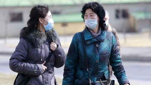 Locals in Pyongyang wearing protective masks.