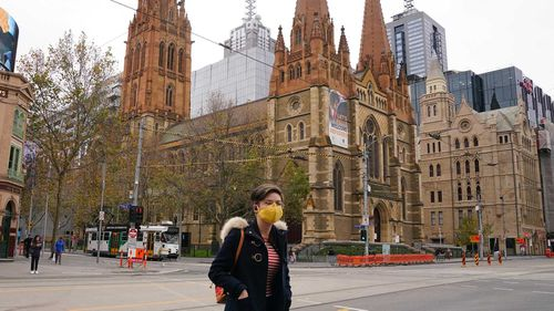 A woman walks past Melbourne's St Paul's Cathedral while wearing a face mask.