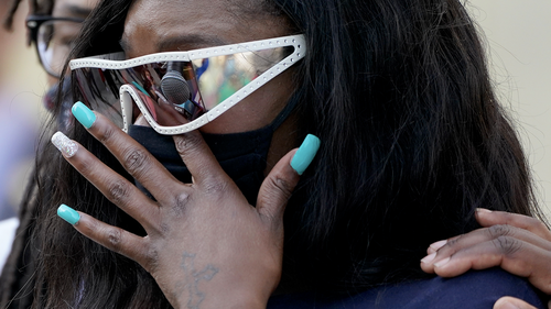 Deja Stallings wipes away tears during a news conference outside city hall Thursday, Oct. 8, 2020, in Kansas City, Mo. Protesters have occupied the lawn and plaza in front of city hall more than a week demanding the resignation of police chief Rick Smith and the officer who knelt on Stallings back while arresting the pregnant woman last week. (AP Photo/Charlie Riedel)