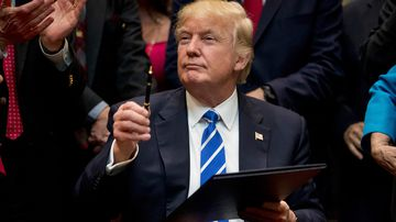 """President Donald Trump holds up a pen he used to sign one of various bills in the Roosevelt Room of the White House in Washington. Ignoring fresh threats from the White House, city leaders across the U.S. are vowing to intensify their fight against Trump's promised crackdown on so-called """"sanctuary cities"""" despite the financial risks. (AAP)"""