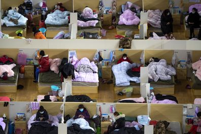 Patients infected with the coronavirus take rest at a temporary hospital converted from Wuhan Sports Center in Wuhan in central China's Hubei Province.