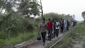 Migrants walk on train tracks on their journey from Central America to the US border in Palenque, Chiapas state, Mexico, Wednesday, Febuary 10, 2021.