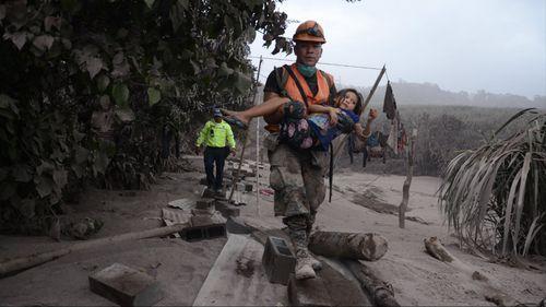 A Guatemalan rescue team worker carries a girl in El Rodeo, Escuintla. (AAP)