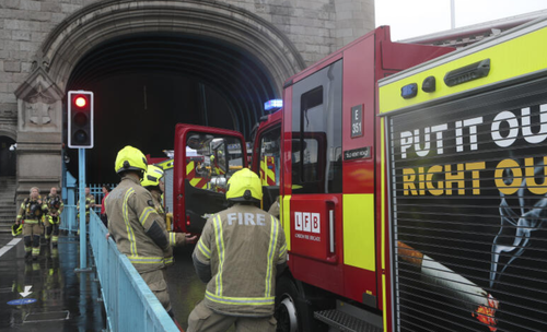 Fire bridge staff speak next to their fire engines parked on Tower Bridge on the River Thames in London, Monday Aug. 9, 2021. London's Tower Bridge was stuck with its roadway arms raised Monday afternoon, snarling traffic on both sides of the River Thames.