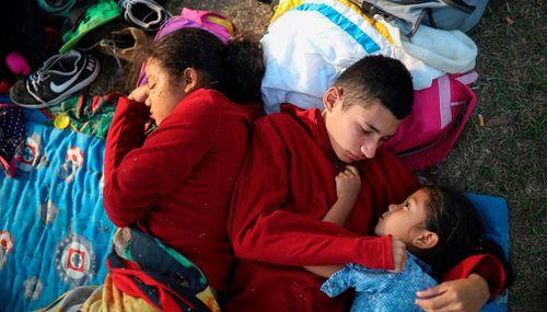 The Zelaya siblings from El Salvador huddle together on a soccer field. (AP)
