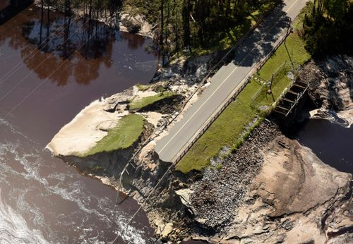 The dam and roadway at Alton Lennon Drive in Boiling Spring Lakes, North Carolina is washed away.