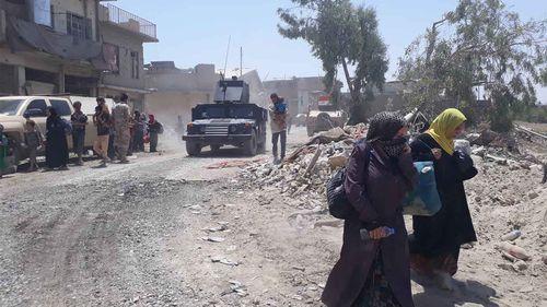 Mosul residents walking down the street. (Owen Holdaway)