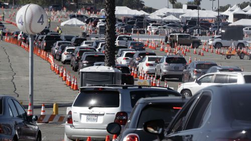 Cars wait in line as they enter a COVID-19 vaccination site at Dodger Stadium in Los Angeles.