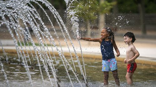 Children cool off in a fountain in a park during a heatwave in Madrid, Spain, Saturday, August 14, 2021. (AP Photo/Andrea Comas)