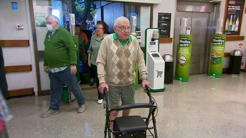 An elderly man arrives at Woolworths to collect essential items before the general public arrives.
