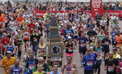 Lukas Bates wearing a costume of Big Ben runs with the crowd towards the finish line of the 39th London Marathon in London, Sunday, April 28, 2019.