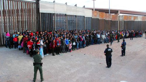 A group of migrants are gathered together after they crossed the border into the USA.