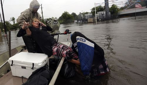 Rhonda Worthington is lifted into a boat while on her cell phone with a 911 dispatcher after her car become stuck in rising floodwaters. (AP)
