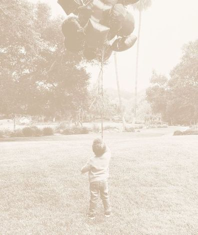 In the photo Archie is standing with his back to the camera holding a large bunch of balloons.