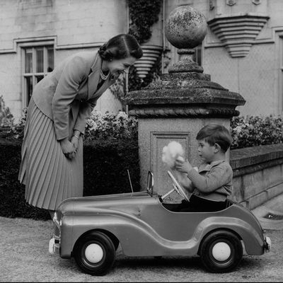 1952:Queen Elizabeth watches her son Charles playing in a miniature car in the grounds of Balmoral Castle
