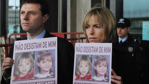 "Gerry (L) and Kate McCann pose with boards portraiting their missing daughter Madeleine reading ""don't give me up"" as they leave the Tribunal Civil de Lisboa in Lisbon on February 10, 2010,"