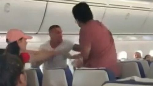 Footage of the incident shows some passengers struggling to restrain a man acting aggressively on Scoot flight TR7.