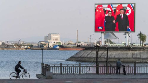 A giant video screen plays a loop of Chinese President Xi Jinping meeting with North Korean Leader Kim to residents and potential investors in Dandong, China, across the river from North Korea.